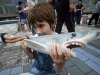 A young activist bites a rubber shark fin during the Hong Kong Shark Foundation, freezemob at Avenue of Stars in Hong Kong, 15 May 2011.The HKSF is calling for all Hong Kong's resident to say no to shark fin soup. Around 73 million sharks are being killed each year for their fins to satisfy Asian demand for the infamous luxury culinary dish. EPA/Paul Hilton